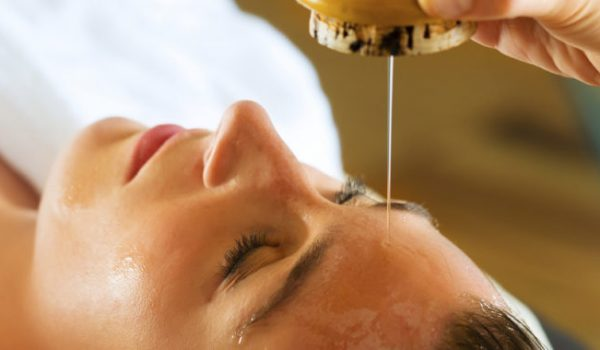 Woman enjoying a Ayurveda oil massage treatment in spa